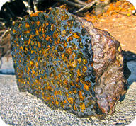 Meteorite containing the mafic minerals olivine and pyroxene, as well as metal flakes similar to the material that separated into the Earth's core and mantle