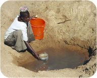 Girl getting water from a hole in the ground