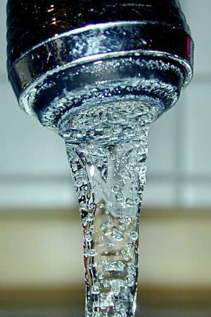 Clean drinking water flowing from a faucet.