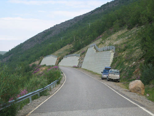 A rock wall stabilizes a slope that has been cut away to make a road