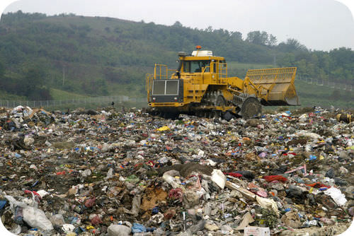 A bulldozer crushes a mountain of trash