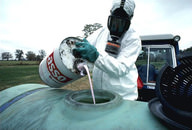 Worker wearing safety gear and pouring a chemical pesticide