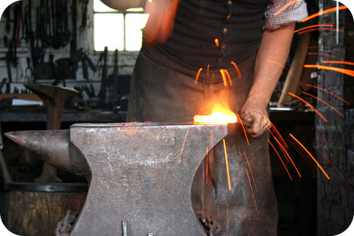 Metal worker shaping iron on an anvil