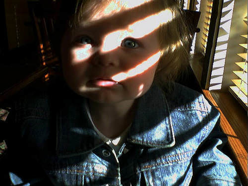 child with sun coming through the blinds
