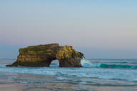 A sea arch creates a natural bridge in California