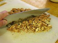 Knife cutting through nuts