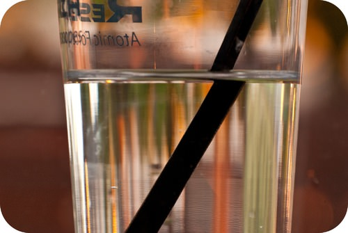 A straw looks bent in a glass of water due to refraction