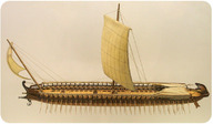 A photo of a wooden model of a Greek ship that has both sails and oars.